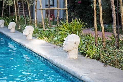 statues of heads along length of pool